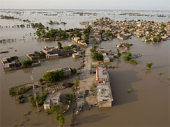 Stranded people stand on a small strip of road waving to a helicopter before being evacuated by the Pakistan Army as flood waters continue to cause suffering two weeks after flooding began, Aug. 12, 2010 in Mirpur Buriro, Pakistan.