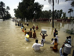 Stranded Pakistanis wade through water for safe areas in Muzaffargarh near Multan, Pakistan, Aug. 13, 2010. Fever, stomach problems and skin diseases are spreading among Pakistani flood victims.