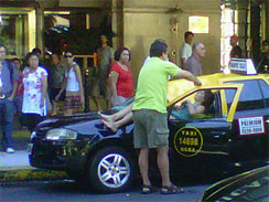 In this cell phone photo provided by Infobae.com received via Twitter from @denisitabaires , a woman lies over a taxi after falling from the 23rd floor of a hotel in downtown Buenos Aires, Argentina, Jan. 24, 2011. (AP Photo/Infobae.com,@Denisitabaires)