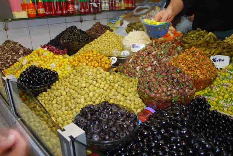 Green, brown, yellow, orange, white olives set in bowls in a moroccan market. Man offering bowl of olives.