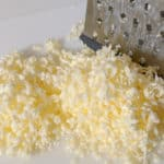 Frozen butter grated with cheese grater on white cutting board