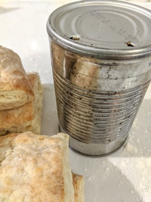 Aluminum can with holes for biscuit cutting and made from scratch buttermilk biscuits on a white countertop