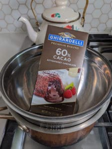 Ghirardelli premium baking 60% cacao bittersweet chocolate bar sitting in a double boiler on the stove