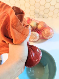 Woman's hand squeezing liquid from onion through orange kitchen towel into blue bowl with bag of yellow onions on the kitchen counter and white hexagonal backsplash