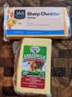 1 package of 365 sharp cheddar cheese and 1 package of organic valley grassmilk organic raw cheddar cheese on a wood cutting board