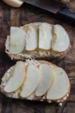Two slices of bread on a wood cutting board layered with camembert cheese and thin apple slices