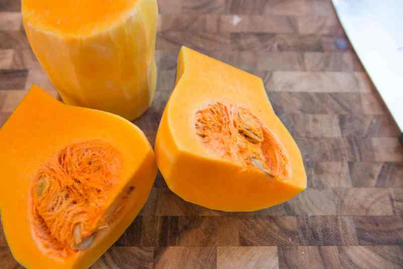 Butternut squash halved and sitting on wood grain cutting board