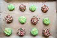 12 unbaked sugar cookies rolled in green, red, and white sprinkles on a sheet pan lined with parchment paper