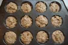 muffin pan filed with healthy banana nut muffin batter topped with chopped walnuts