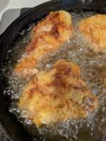 chicken frying in hot oil in cast iron skillet on stove