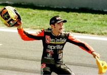 15 settembre 1996: Max Biaggi 'sventola' il casco per festeggiare la vittoria, con l'Aprilia, nella gara delle 250 cc del Gp d' Europa, terzultima prova del campionato mondiale di motociclismo