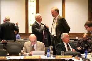 Trustee John MacPherson, at lower right, said trustees voted for open search because of public input and the potential for a law suit if finalists were kept confidential. In the background, Dave Palmerlee talks with trustee Mike Massie of Laramie who wrote the motion to pursue the open search. (Gregory Nickerson/WyoFile)