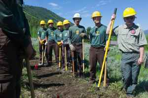 A Montana Conservation Corps Crew listens to U.S. Secretary of Agriculture Tom Vilsack while taking a break from a project on the Bridger-Teton National Forest near Jackson. Crew members get about $1,000 a month for their summer-long jobs. (Angus M. Thuermer Jr./WyoFile)