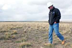 Jonah Energy's Paul Ulrich inspects a former drill pad that was replanted with native vegetation about five years ago. The region's arid climate makes it difficult to recover plant life after a disturbance. (photo by Phil Taylor)
