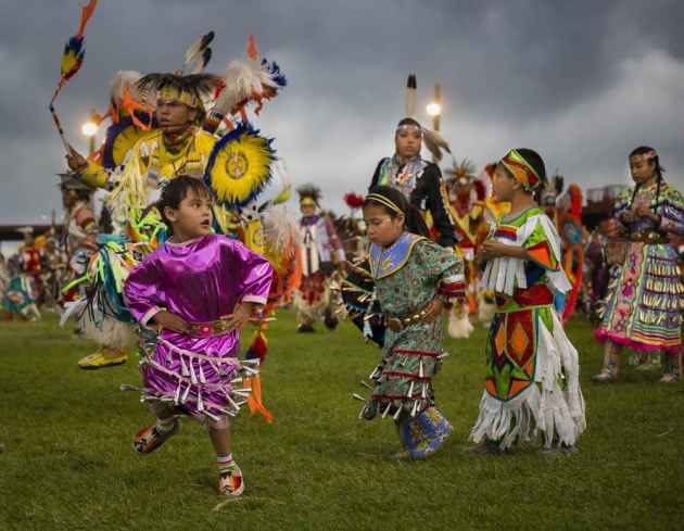 Carmya Sage (girl in pink dress), age 3, dances in the Saturday evening Grand Entry at the Eastern Shoshone Indian Days Powwow, Fort Washakie, Wyoming on June 27, 2015, (Terance Oldman)