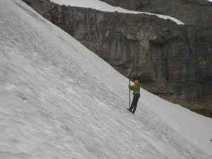 A member of theJenny Lake Climbing Rangers helps take measurements on the Schoolroom Glacier in 2014. (courtesy Grand Teton National Park)