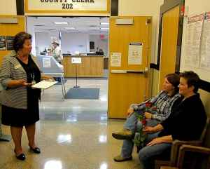 Albany County Clerk Jackie Gonzales explains the process for applying for a marriage license to Teresa Bingham and Linda Mahaffey. (WyoFile/Gregory Nickerson)