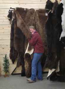 """Barb Heinze hugs a buffalo hide in Merlin's Hide Out, the shop she owns with her husband, Merlin. The shop is known for its buffalo hides and built the coats worn by Kurt Russell in the movie """"The Hateful Eight."""" (courtesy)"""