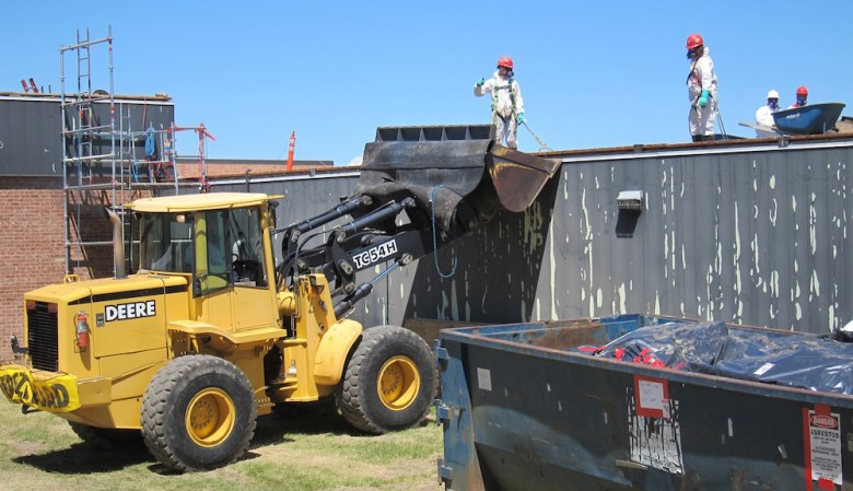 A crew performs work on the roof of Kelly Walsh High School in Casper. Some companies fined by Wyoming OSHA don't even bother to pay. Those unpaid penalties since 2009 total $139,000. (Dustin Bleizeffer/WyoFile)
