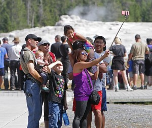 Visitors take a selfie at Old Faithful in August 2015. Social media and technolgoy has changed the way visitors interact with the park, staff say. (Photo courtesy Jim Peaco.)