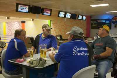A bowling team at the Tuesday night Cowboy Bowling League in Gillette. Behind them are empty chairs and tables. The shrinking league is down ten guys from the year before.