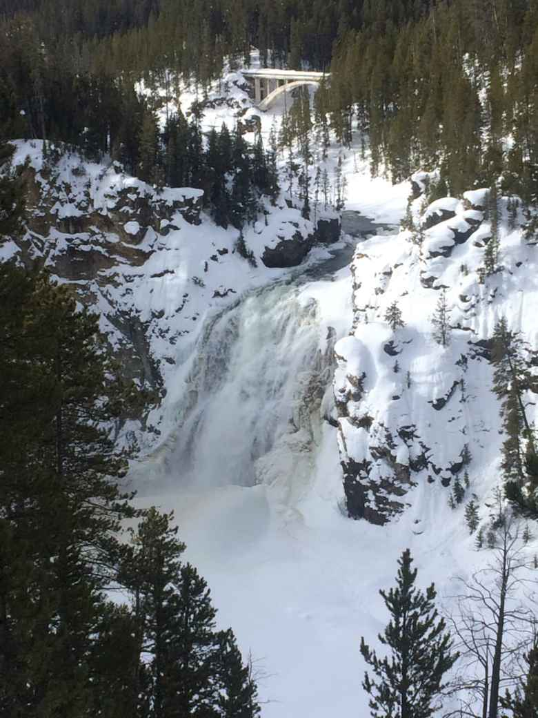 The Upper Falls of the Yellowstone River are rimmed with snow and ice in the winter. Overlooks are empty. (Kelsey Dayton/WyoFile)