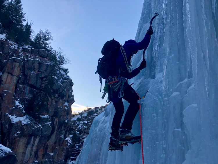 Wyoming Mountain Guides' ice climbing guide Zach Lentsch leads a pitch of WI3+ ice in the central gorge of Shell Canyon in January 2019