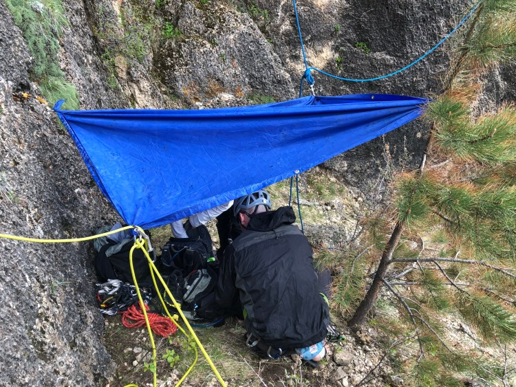Clients use a rope tarp to protect themselves from an unexpected hail storm while climbing in Crazy Woman Canyon