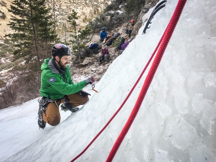 Lead ice climbing guide Zach Lentsch demonstrates proper ice screw placement during a clinic in the Bighorn Mountains in February 2020