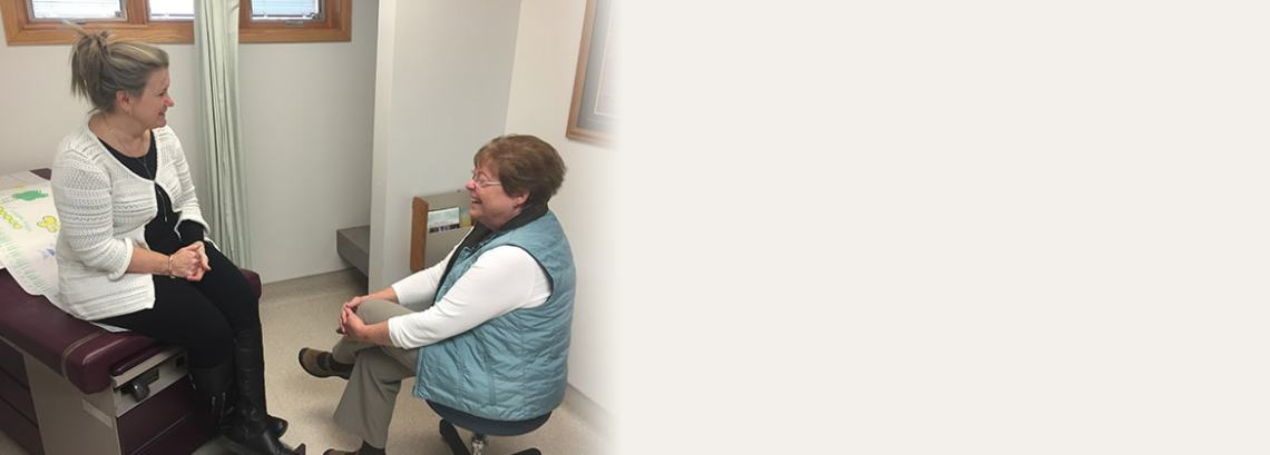 Mary E. Williams, NP-C consults with a patient in the exam room