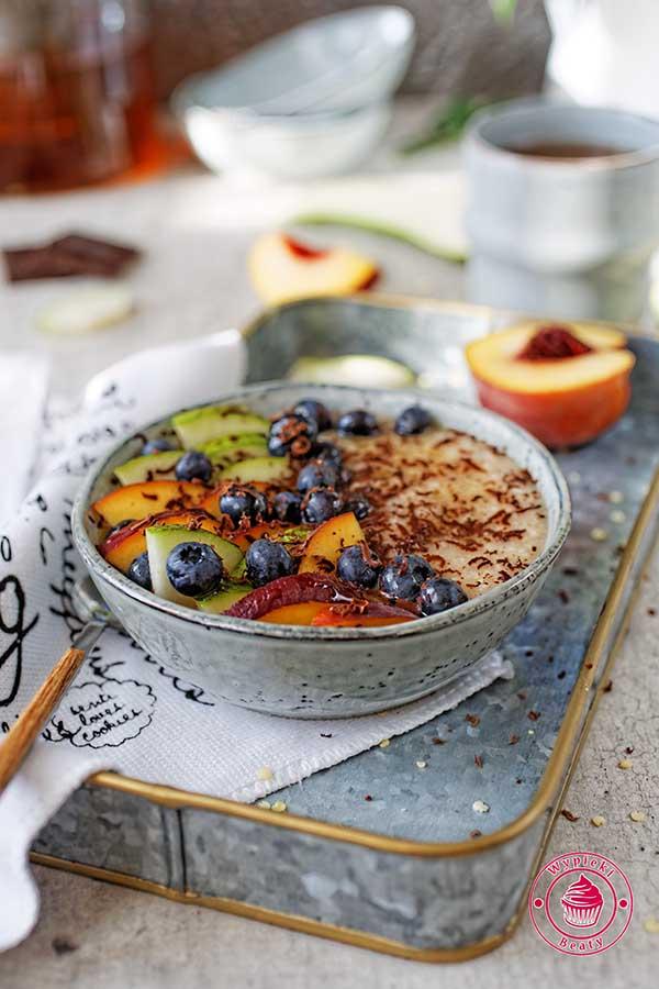 zdrowe śniadanie z płatków owsianych, gruszek, brzoskwiń i borówek razem z miodem i gorzką czekoladą