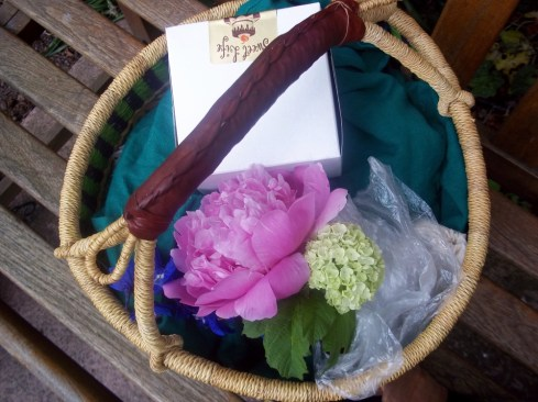 offering basket with a nosegay of flowers and bakery box