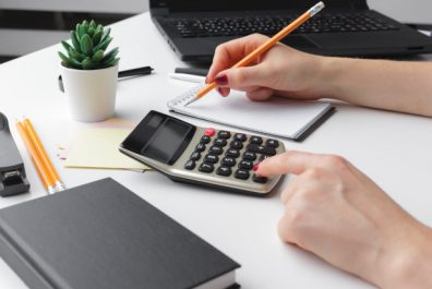 business-woman-working-with-financial-data-hand-using-calculator_127657-7329