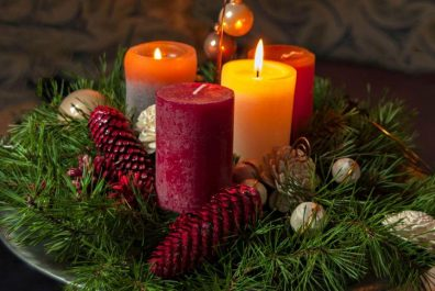 high-angle-view-of-candles-with-pine-cones-and-wreath-on-table-766397041-5b63894a46e0fb0025a917fa
