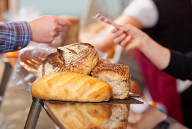 Customer Paying For Breads At Bakery Counter