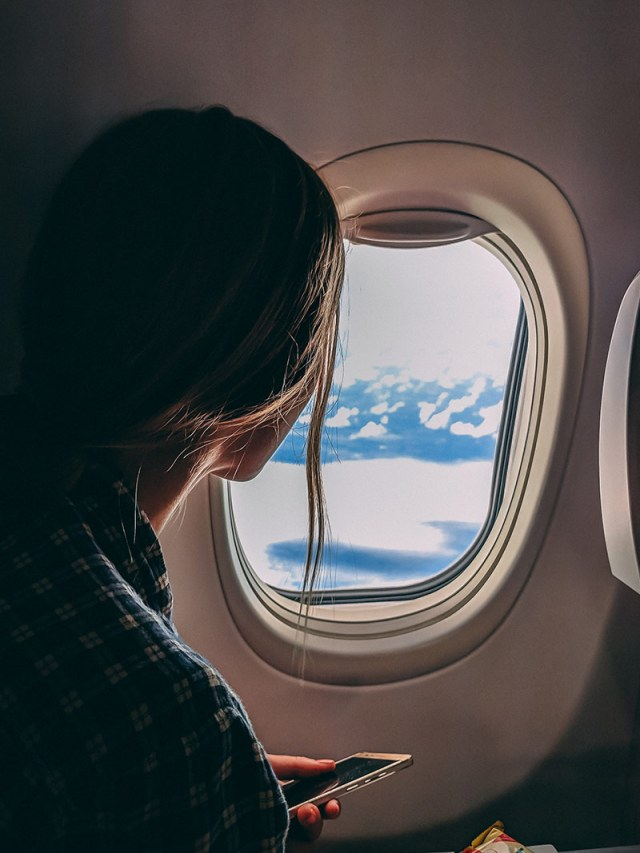 Girl looking out of the window on a flight from Perth to Lombok