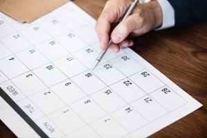 person pinpointing pen on calendar