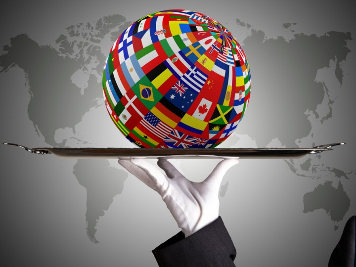 Globe made up of international flags balanced on a silver tray