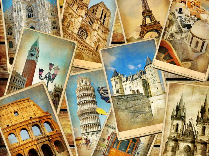 Multiple travel postcards on wooden surface