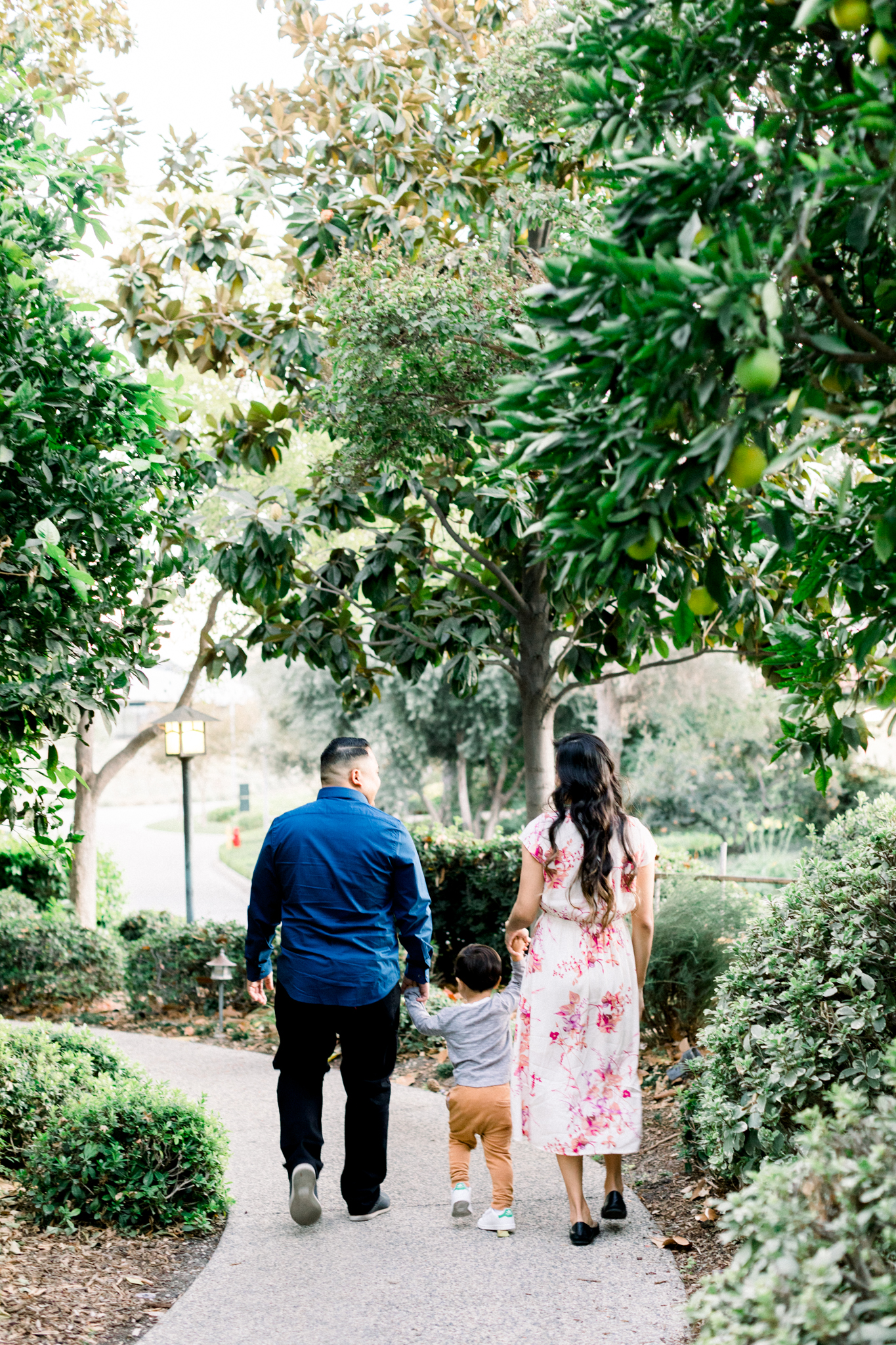The Gomez family walking down a path in Cal Poly during their family photography session.