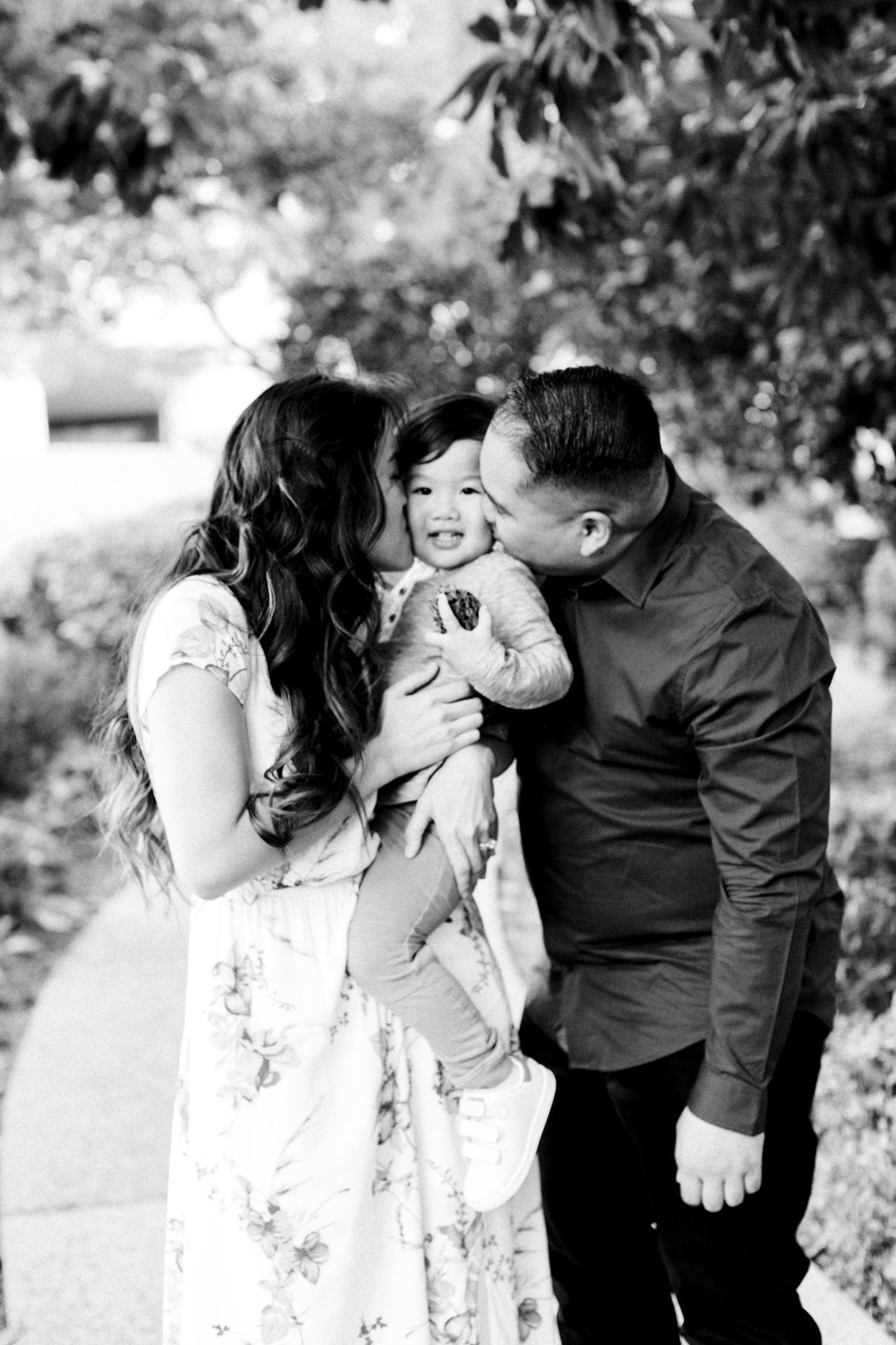 Two parents kissing their son's cheeks during a family photography session.