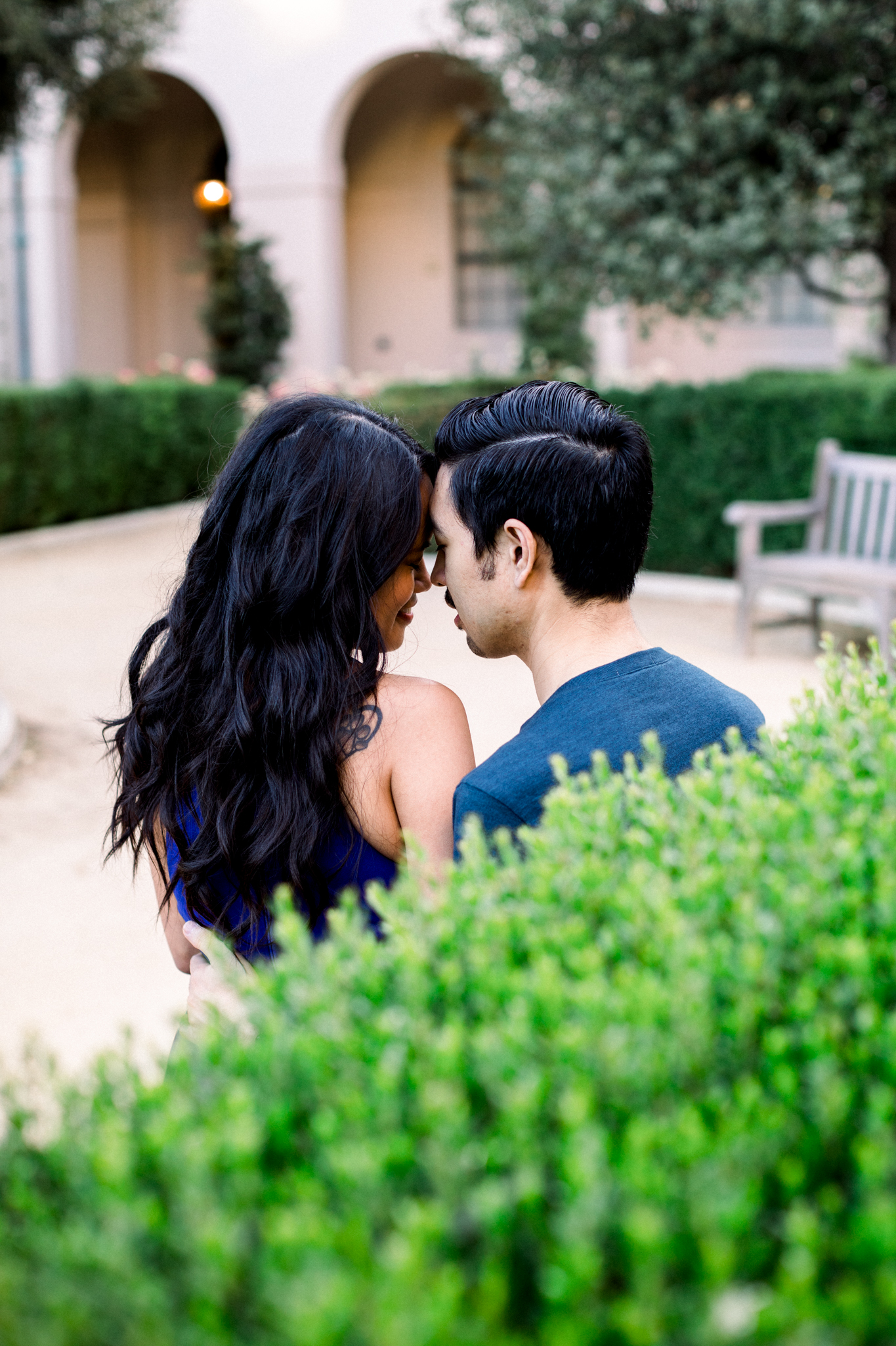 A couple sitting in front of Pasadena City Hall during their engagement session.