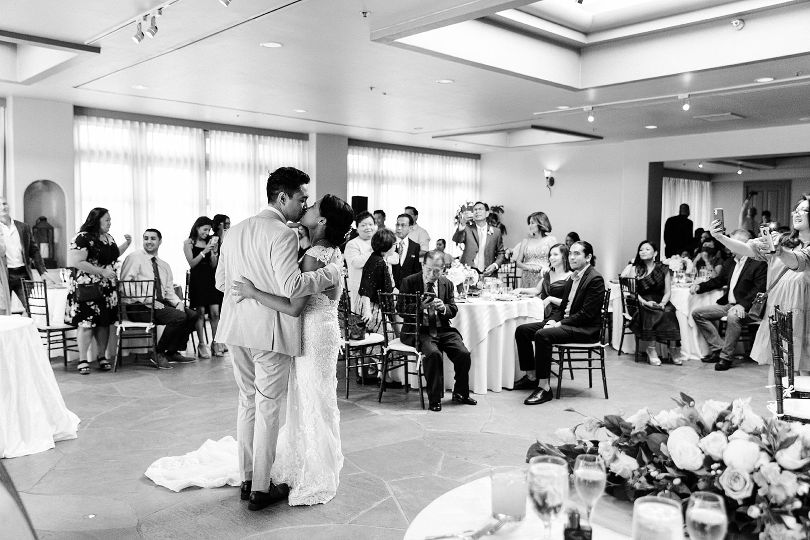 A bride and groom dancing and laughing during their wedding in Costa Mesa.