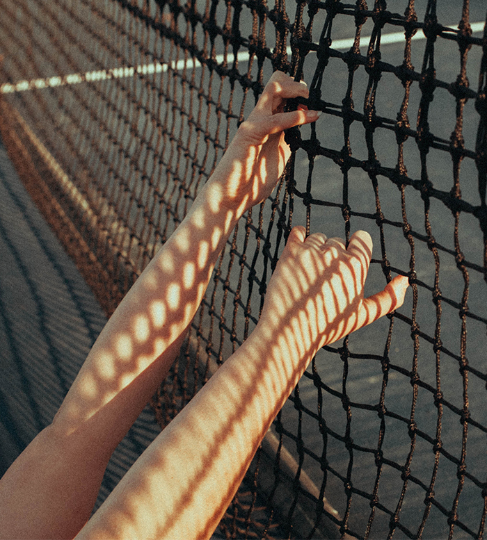 closeup of hands with shadows on tennis court