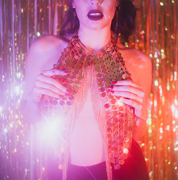 girl wearing shiny metal bra shirt with neon lights