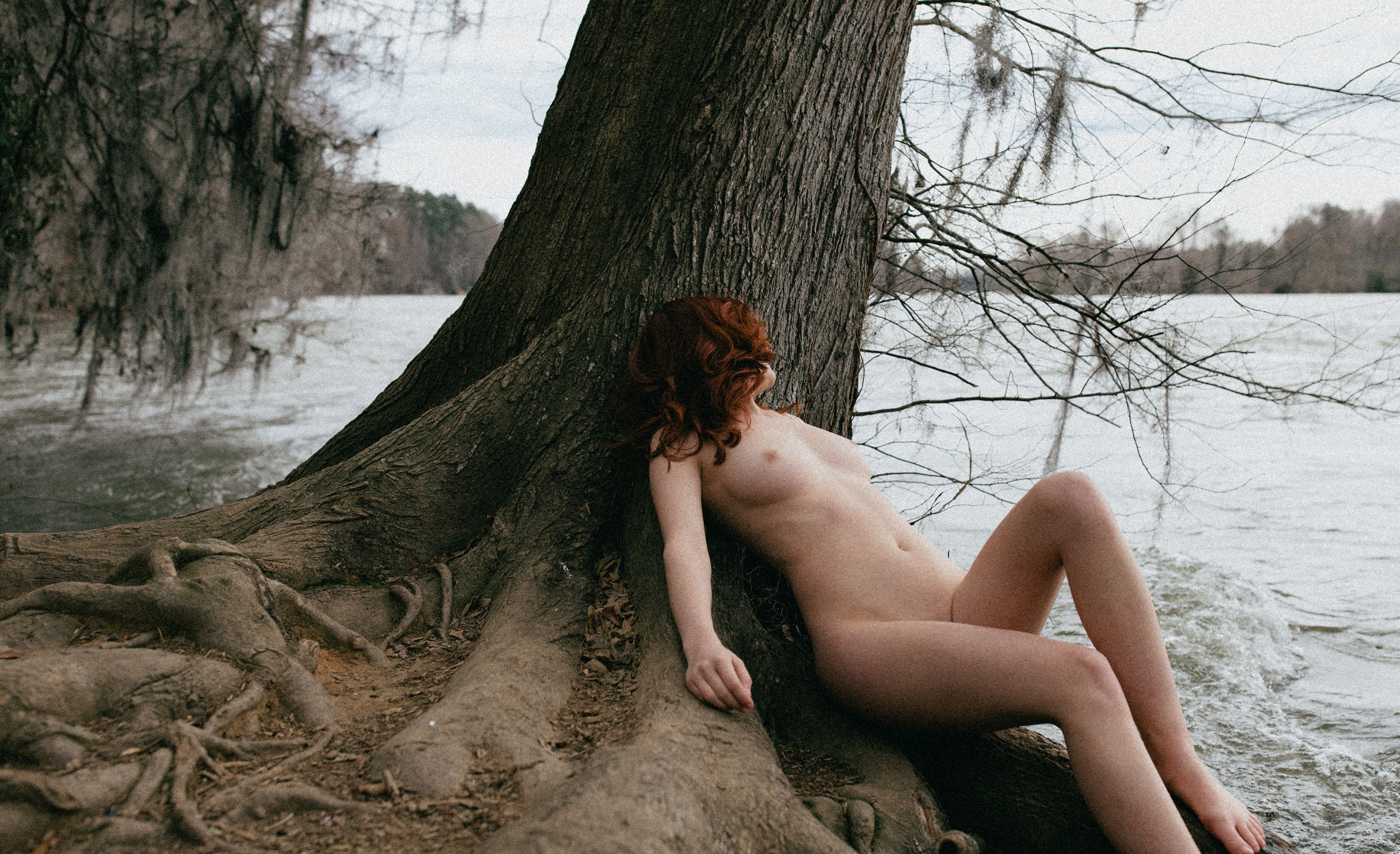 nude woman laying on tree next to river