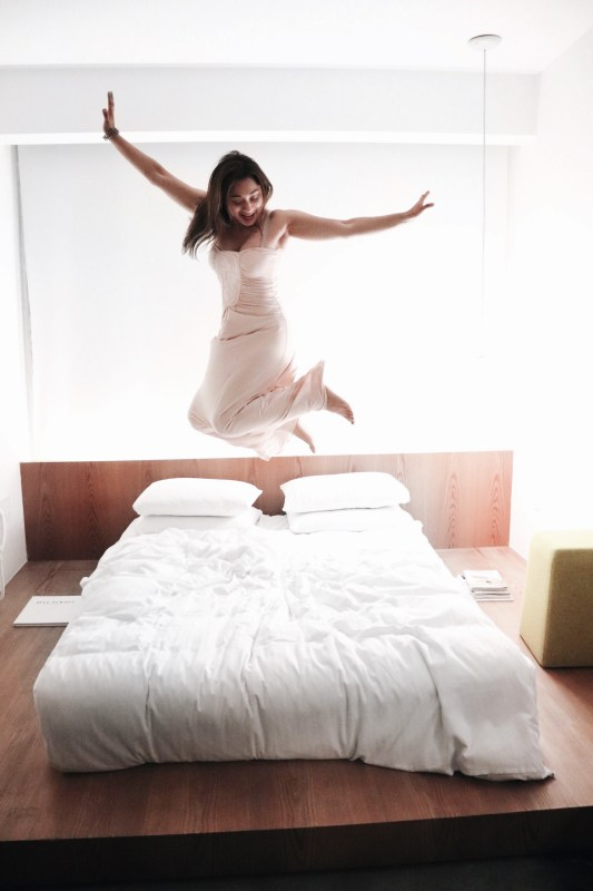girl jumping in hotel bed
