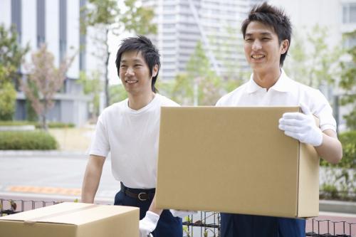 笑顔で段ボール箱を運ぶ2人の引越し業者スタッフ