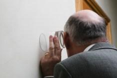 壁に耳を当て隣りの部屋を盗聴する老人男性