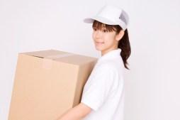 ダンボールを運ぶ引越し業者の女性スタッフ